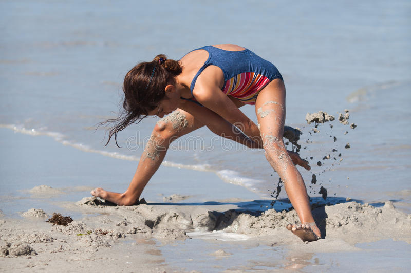 Cute young girl digs a hole in the sand stock images