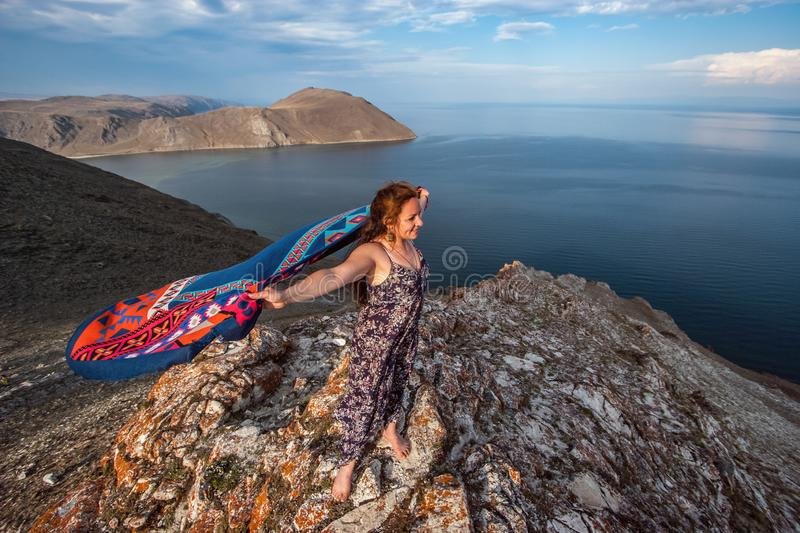 A cute young girl in a dress with a colorful scarf fluttering behind stands on a rock above Lake Baikal. royalty free stock photo