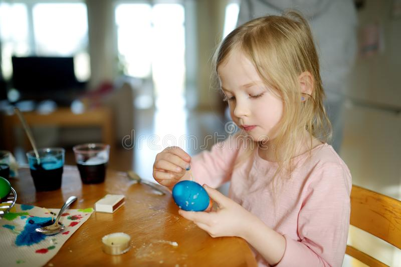 Cute young girl dyeing Easter eggs at home. Child painting colorful eggs for Easter hunt. Kid getting ready for Easter celebration. Family traditions royalty free stock image