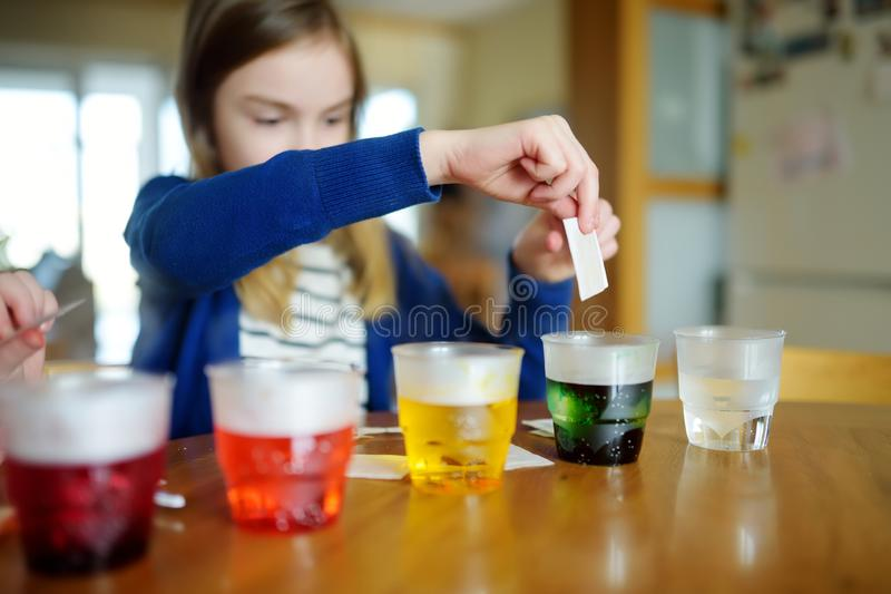Cute young girl dyeing Easter eggs at home. Child painting colorful eggs for Easter hunt. Kid getting ready for Easter celebration. Family traditions stock photography