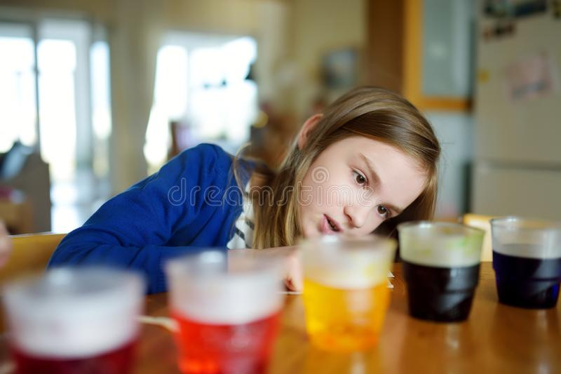 Cute young girl dyeing Easter eggs at home. Child painting colorful eggs for Easter hunt. Kid getting ready for Easter celebration. Family traditions stock photos
