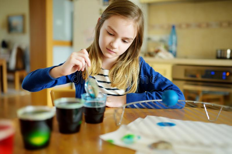 Cute young girl dyeing Easter eggs at home. Child painting colorful eggs for Easter hunt. Kid getting ready for Easter celebration. Family traditions stock images