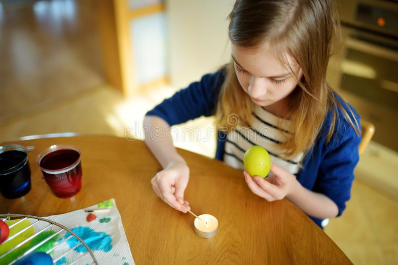 Cute young girl dyeing Easter eggs at home. Child painting colorful eggs for Easter hunt. Kid getting ready for Easter celebration. Family traditions royalty free stock photo