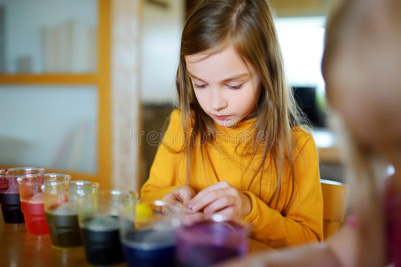 Cute young girl dyeing Easter eggs at home. Child painting colorful eggs for Easter hunt. Kid getting ready for Easter celebration royalty free stock images