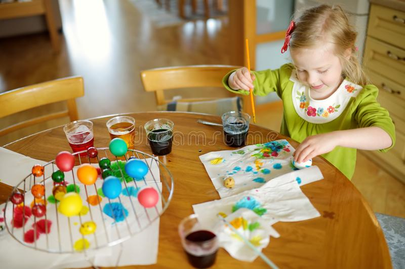 Cute young girl dyeing Easter eggs at home. Child painting colorful eggs for Easter hunt. Kid getting ready for Easter celebration. Family traditions royalty free stock photos