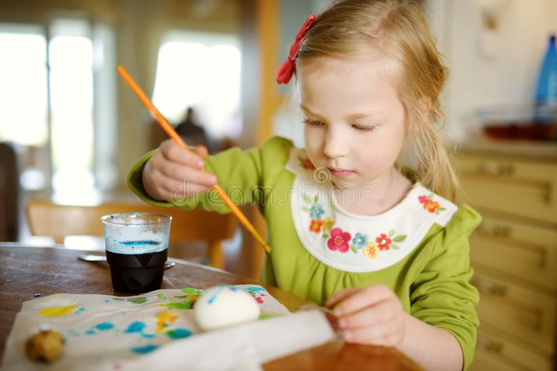 Cute young girl dyeing Easter eggs at home. Child painting colorful eggs for Easter hunt. Kid getting ready for Easter celebration. Family traditions royalty free stock photography