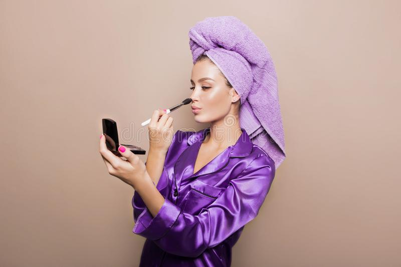 Cute young girl with fresh glowing skin and turban on her head in velvet pajamas on the beige background is looking into stock photo