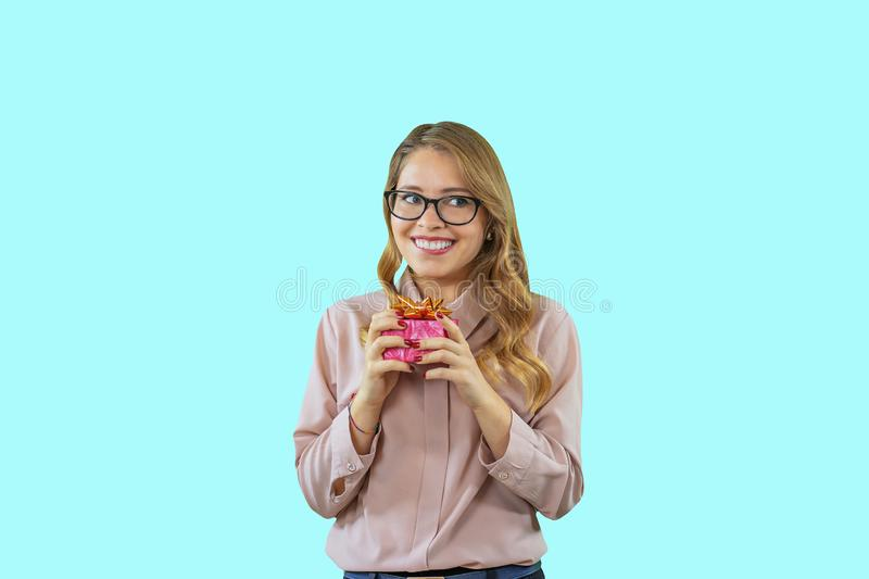 A cute young girl with glasses and a pink blouse is holding a gift while smiling while waiting and looking sideways by stock photos