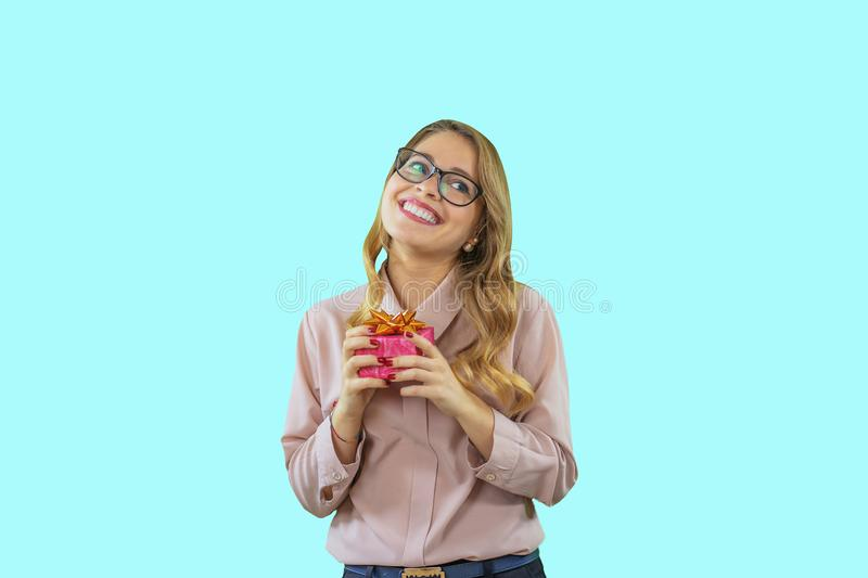 A cute young girl with glasses and a pink blouse is holding a gift while smiling while waiting and looking up to the stock images
