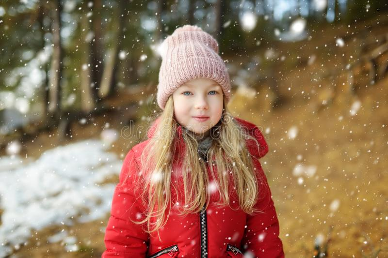 Cute young girl having fun during forest hike on beautiful winter day. Active family leisure with kids stock images