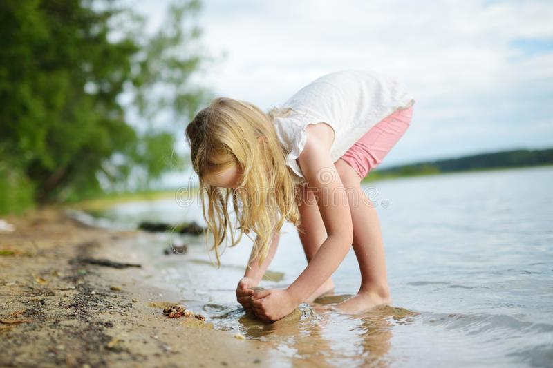 Cute young girl having fun on a sandy lake beach on warm and sunny summer day. Kid playing by the river. Summer activities for children royalty free stock image