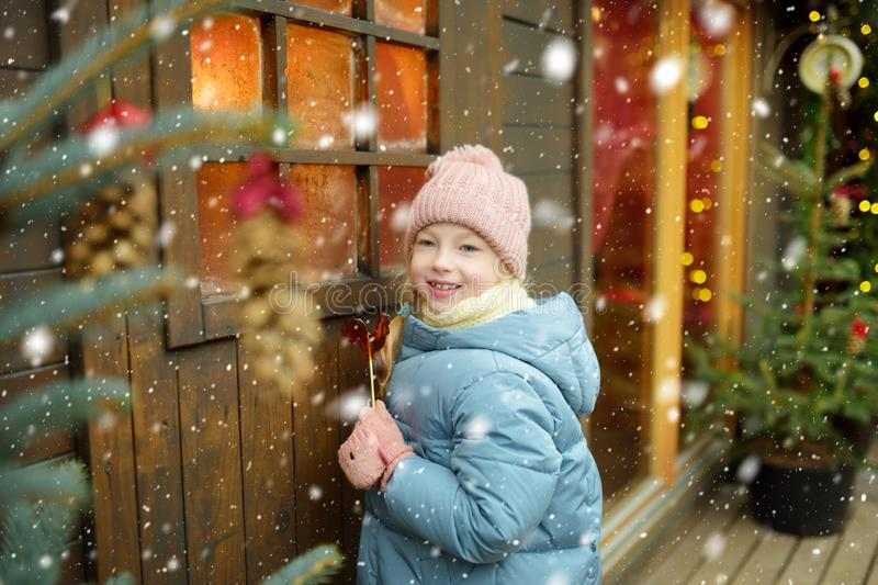 Cute young girl having rooster-shaped lollipop on traditional Christmas fair in Riga, Latvia. Child enjoying sweets, candies and royalty free stock photos