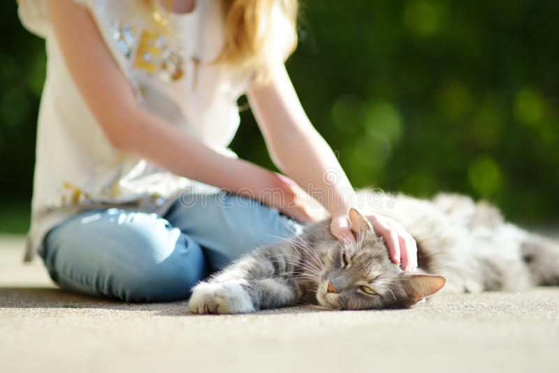 Cute young girl with her cat on sunny autumn day. Adorable child petting her kitty royalty free stock photos