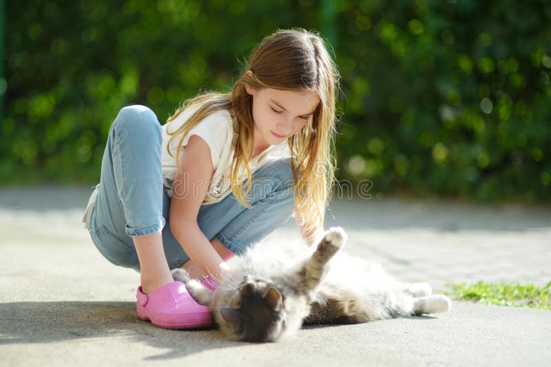 Cute young girl with her cat on sunny autumn day. Adorable child petting her kitty stock image