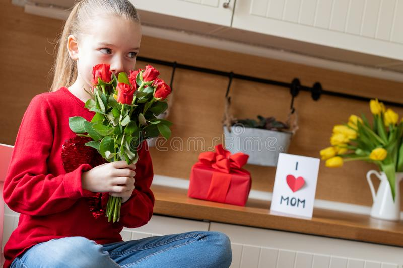 Cute young girl holding bouquet of red roses for her mom. Family celebration concept. Happy Mother`s Day or Birthday Background. royalty free stock photo