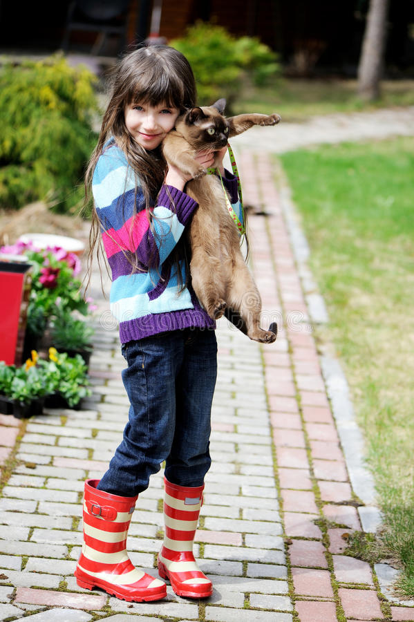 Cute young girl holding her kitty royalty free stock images