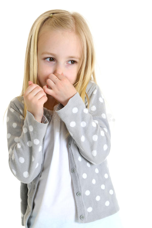 Cute young girl holding her nose from a bad smell stock image