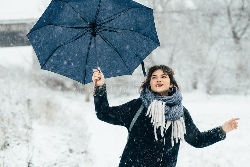 A cute young girl holds umbrellas in the hands of the winter season. Winter portrait of young beautiful brunette woman. A cute young girl holds umbrellas in the royalty free stock photography