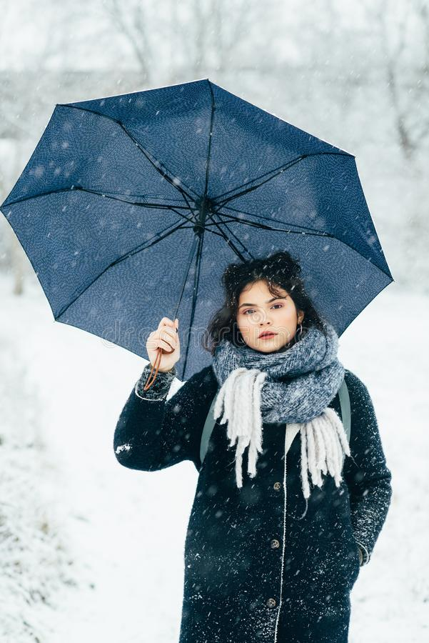 A cute young girl holds umbrellas in the hands of the winter season. Winter portrait of young beautiful brunette woman. A cute young girl holds umbrellas in the royalty free stock photo