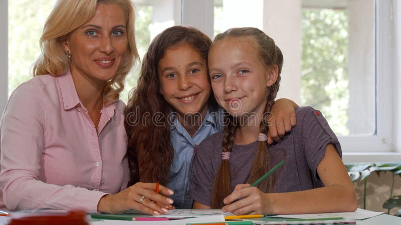 Cute young girl joining her classmate and art teacher in working on a project stock photos