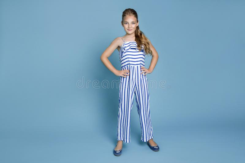 Cute young girl with long blond hair dressed in a white and blue striped outfit standing on a white background royalty free stock image