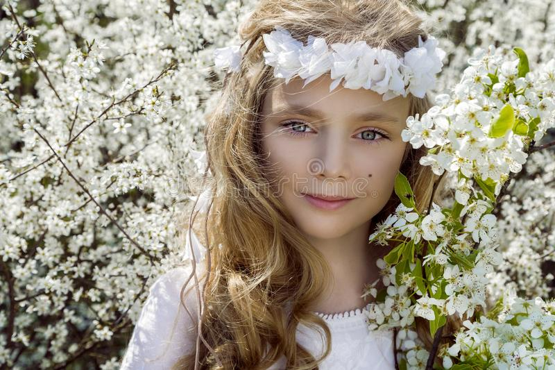 Cute young girl with long blond hair standing in a meadow in wreath of flowers, holding a bouquet of spring flowers royalty free stock images