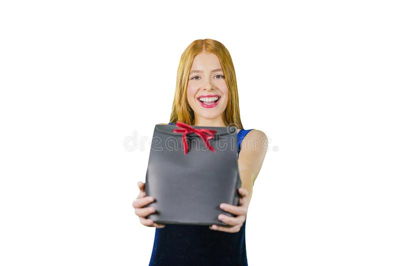 A cute young girl with long red hair is holding a black exclusive box with a gift and smiling at the camera. The concept stock photography