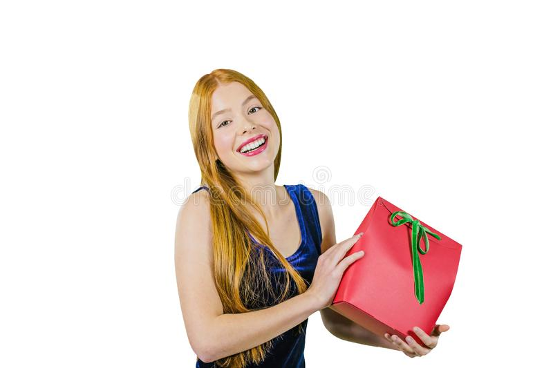 A cute young girl with long red hair is holding a red exclusive box with a gift and smiling at the camera. The concept royalty free stock image