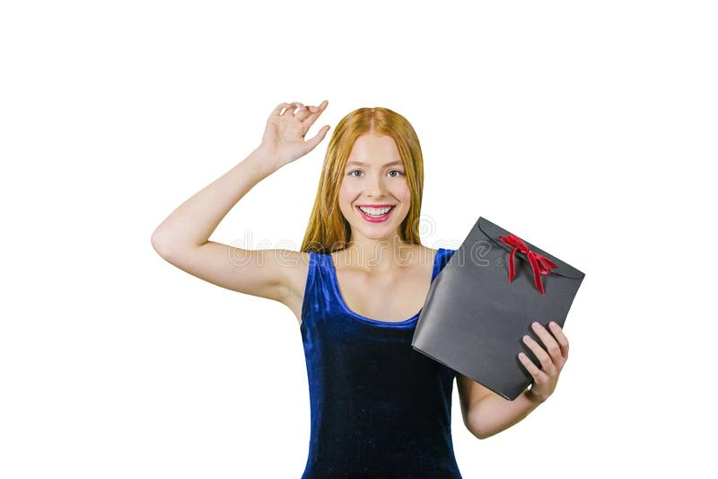 A cute young girl with long red hair holds in one hand a gift in a black box with a red velvet ribbon, and with her stock images