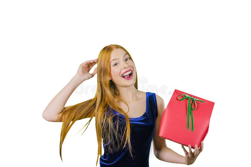 A cute young girl with long red hair holds in one hand a red box with a gift, while the other hand straightens her royalty free stock images