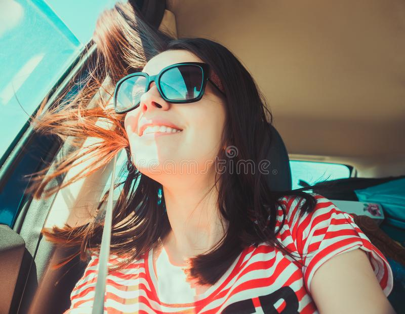 Cute young girl is looking out the window of a car laughing. Hair develops in the wind stock photography