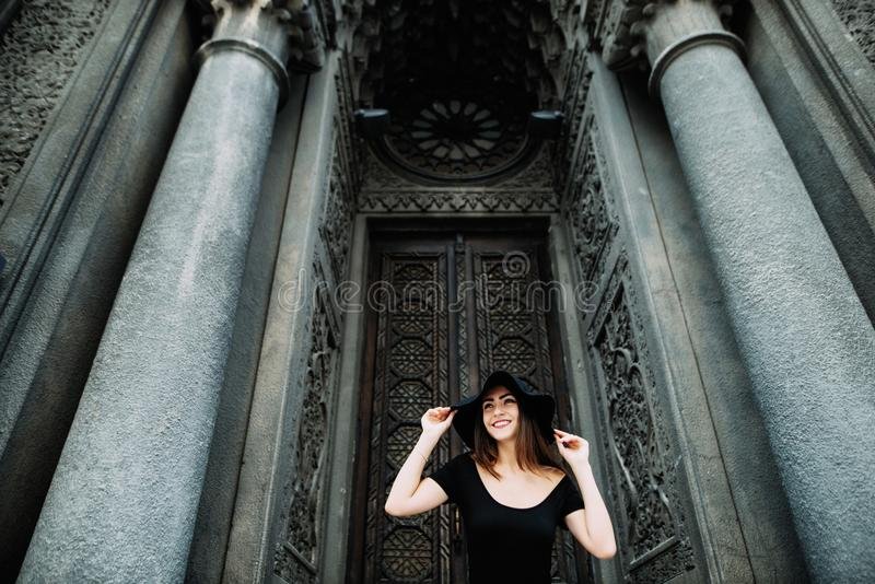 Cute young girl modeling appearance posing against the backdrop of huge beautiful doors in black dress and hat stock photos