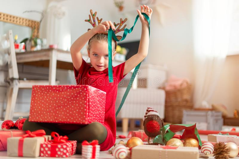 Cute young girl opening large red christmas present while sitting on living room floor. Candid family christmas time. Cute young girl opening large red royalty free stock photo