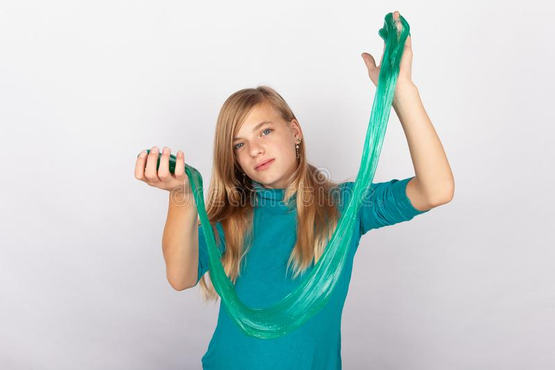 Cute young girl playing with green slime looks like gunk stock photo