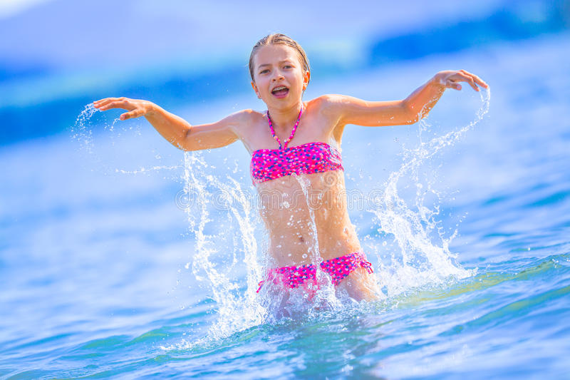 Cute young girl playing in the sea. Happy pre-teen girl enjoys summer water and holidays in holiday destinations royalty free stock photos