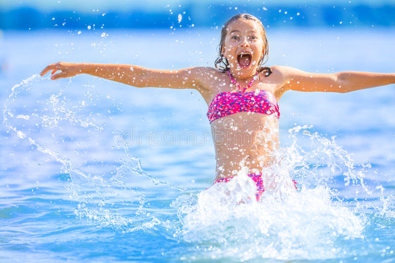 Cute young girl playing in the sea. Happy pre-teen girl enjoys summer water and holidays in holiday destinations royalty free stock image