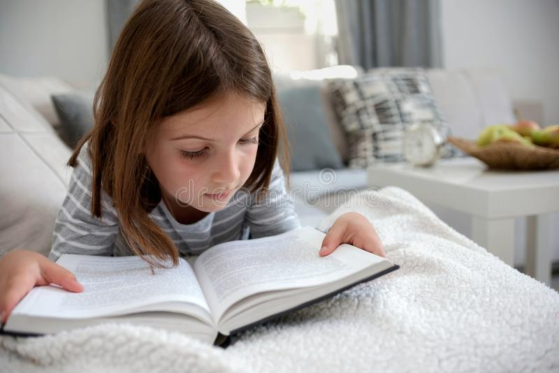 Cute young girl reading book at home stock images