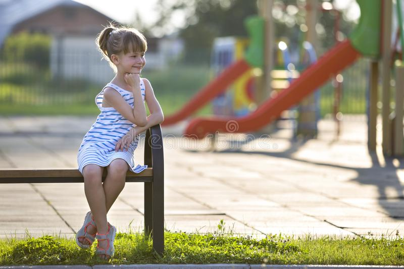 Cute young girl in short dress sitting alone outdoors on playground bench on sunny summer day royalty free stock images