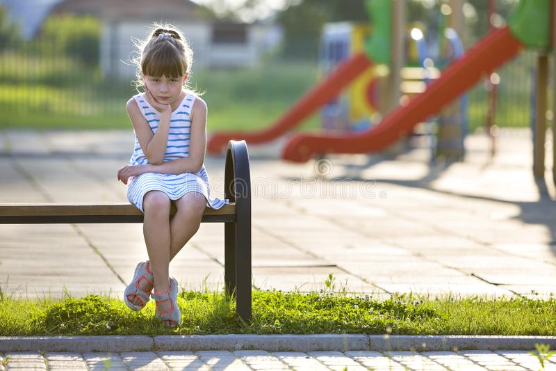 Cute young girl in short dress sitting alone outdoors on playground bench on sunny summer day royalty free stock photography