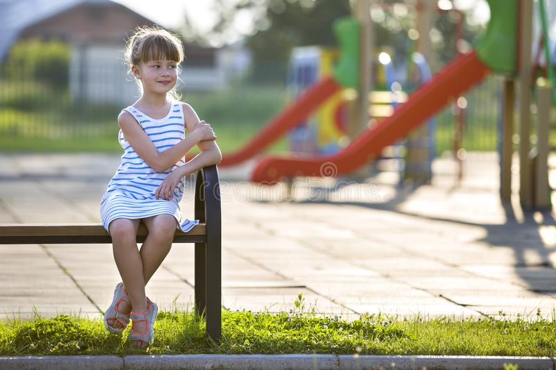 Cute young girl in short dress sitting alone outdoors on playground bench on sunny summer day royalty free stock photo