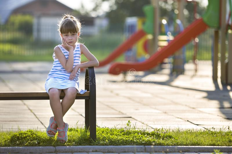 Cute young girl in short dress sitting alone outdoors on playground bench on sunny summer day stock photo