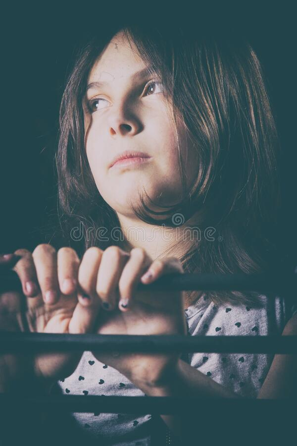 Cute young girl sitting in the dark on a chair royalty free stock photos