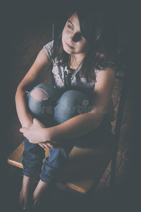 Free Cute Young Girl Sitting In The Dark On A Chair Royalty Free Stock Photos - 183388348