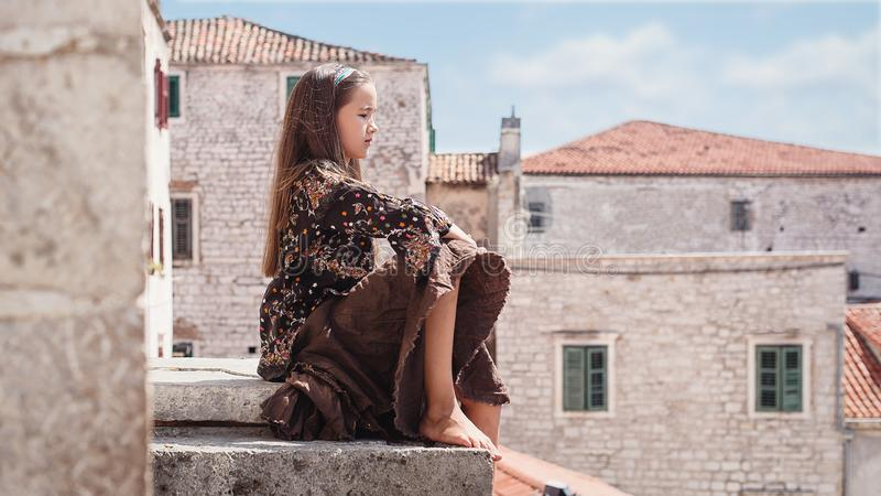 Cute young girl sitting on the roof of the old town. Nice female child in medieval city. royalty free stock images