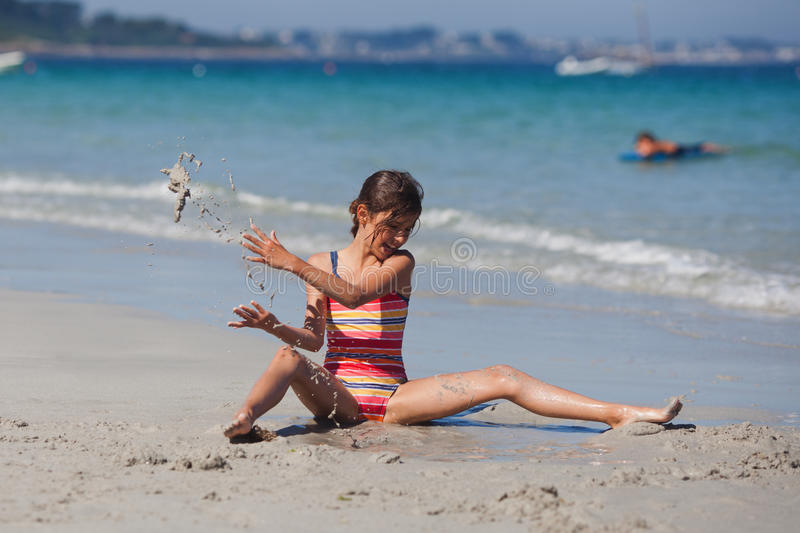Cute young girl sitting in the sand and has fun stock images