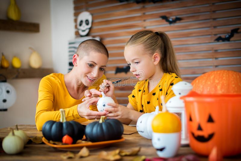 Cute young girl sitting at a table, decorating little white pumpkins with her mother, a cancer patient. DIY Halloween. royalty free stock image