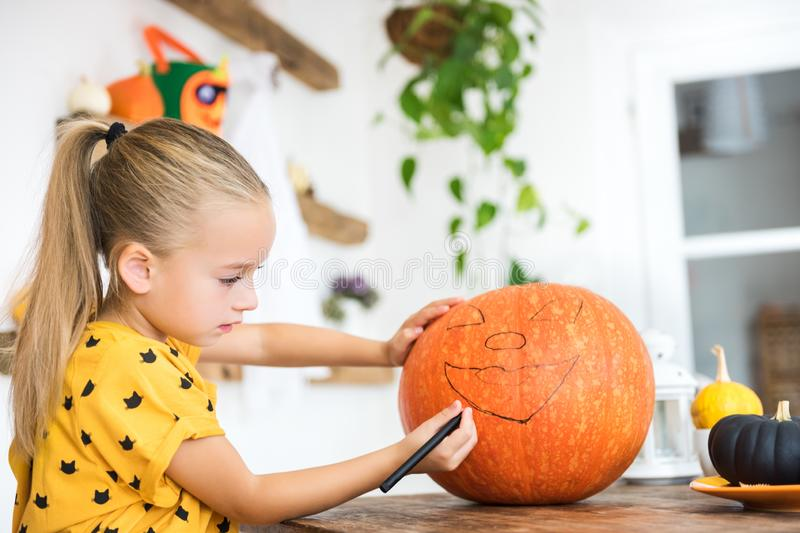 Cute young girl sitting at a table in living room, drawing a face on a large halloween pumpkin. Halloween holiday. royalty free stock photo