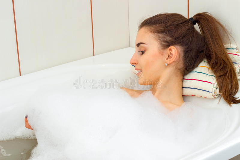 Cute young girl smiling and bathed in a tub with foam royalty free stock photos