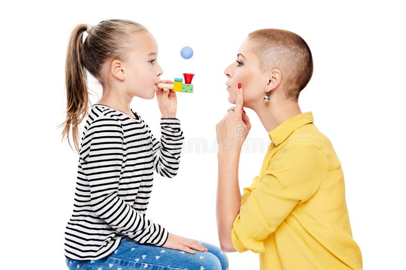 Cute young girl with speech therapist making special exercises at speech therapy office. Child speech therapy concept on white. stock photo