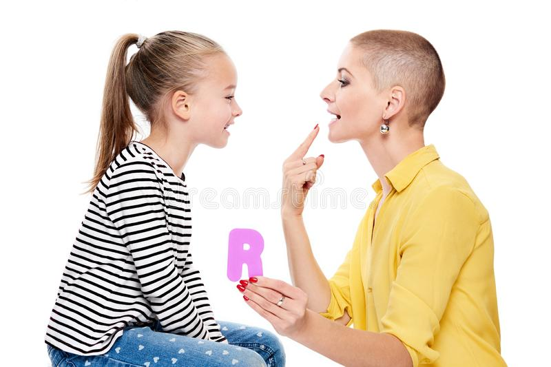 Cute young girl with speech therapist practicing correct pronunciation. Child speech therapy concept on white background. Speech impediment corrective royalty free stock image